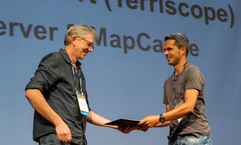 赞助商GeoCat的 Jeroen Ticheler在给FOSS4G开发奖的获得者Thomas Bonfort颁奖